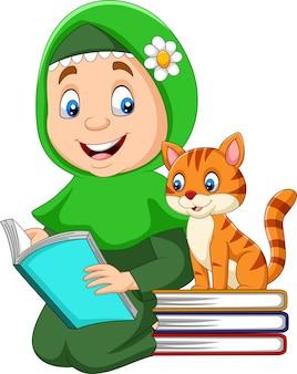 Moslemisches mädchen, das ein buch mit katze liest