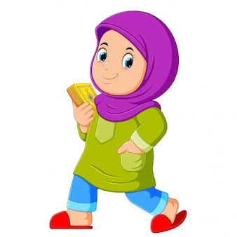 Moslemisches mädchen, das heiligen quran geht und trägt