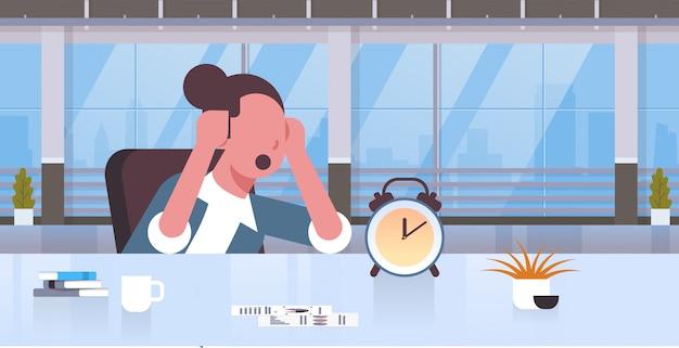 Müde geschäftsfrau, die kopf an händen hält geschäftsfrau, die am arbeitsplatz sitzt und wecker frist zeitmanagementkonzept moderne büroinnenporträtwohnung sucht