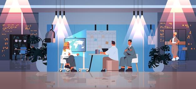 Müde geschäftsleute, die im kreativen coworking-center teamwork-konzept zusammenarbeiten dunkle nacht büroinnenraum horizontal in voller länge