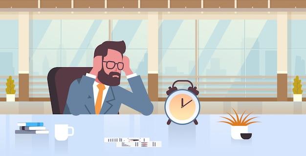 Müder geschäftsmann, der kopf durch zwei hände hält geschäftsmann sitzen arbeitsplatz schreibtisch mit wecker frist zeitmanagement-konzept moderne büro innen männliche cartoon charakter porträt flach