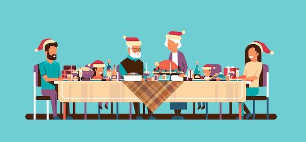 Multi generationsfamilie, welche die feiertagsleute der frohen weihnachten des neuen jahres bei tisch sitzen horizontale ebene des traditionellen abendessenkonzeptes feiert