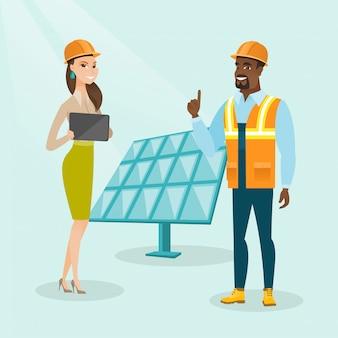 Multiethnische ingenieure, die am solarkraftwerk arbeiten