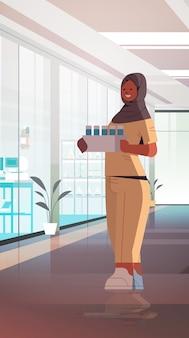 Muslimische ärztin arabische ärztin mit reagenzgläsern medizin gesundheitswesen konzept krankenhaus innenraum in voller länge vertikale vektor-illustration