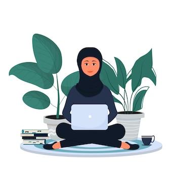 Muslimische arabische frau sitzt und arbeitet mit laptop in traditioneller hijab-kleidung