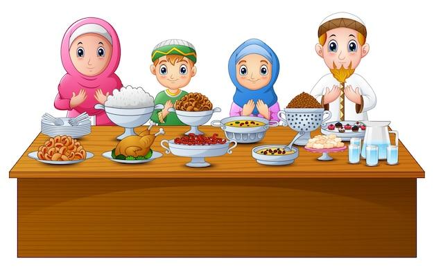Muslimische familie betet zusammen vor dem fastenbrechen