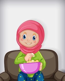 Muslimische frau, die popcorns isst, die auf sofa sitzen