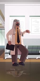 Muslimischer mann arzt in uniform arabischen arabischen medizinischen fachmann stehend im krankenhaus korridor medizin gesundheitswesen konzept in voller länge vertikale vektor-illustration