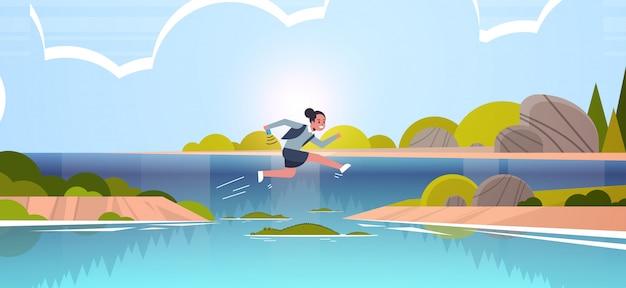 Mutige geschäftsfrau, die über fluss mit krokodilrisiko- und gefahrenoptimismus-bestimmungskonzeptgeschäftsfrau springt, die zum ziellandschaftshintergrund in voller länge flache horizontale läuft