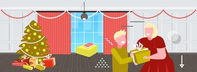 Mutter, die geschenkgeschenkbox zum kleinen sohn frohe weihnachten winterferienfeierkonzept modernes wohnzimmerinnenporträt horizontale vektorillustration gibt