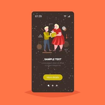 Mutter, die geschenkgeschenkbox zum kleinen sohn frohe weihnachten winterferienfeierkonzept smartphone-bildschirm online mobile app in voller länge vektor-illustration gibt