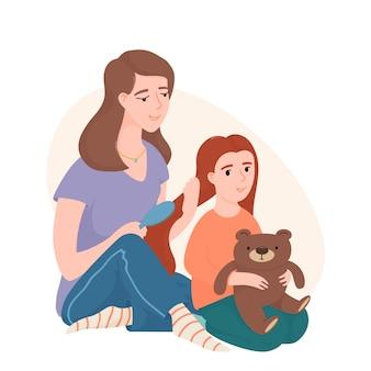 Mutter kämmt ihre kleinen tochterhaare mit einer bürste, beide sitzen auf dem boden. mutter und tochter verbringen zeit miteinander und bürsten sich die haare
