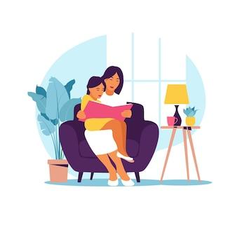 Mutter liest für tochter, die auf dem sofa mit buch sitzt