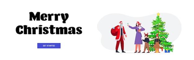 Mutter mit kindern prüft körpertemperatur von santa claus coronavirus quarantäne selbstisolation konzept neujahr weihnachten feiertage feier banner