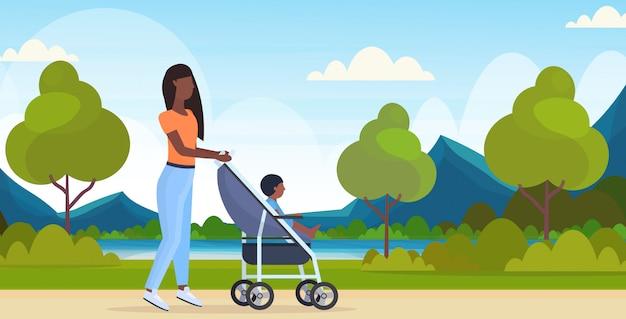 Mutter mit kleinkindsohn im kinderwagen, der frau im freien geht, die kinderwagen mit kind glücklich familie mutterschaft konzept städtischen stadtpark landschaft hintergrund voller länge horizontal schiebt