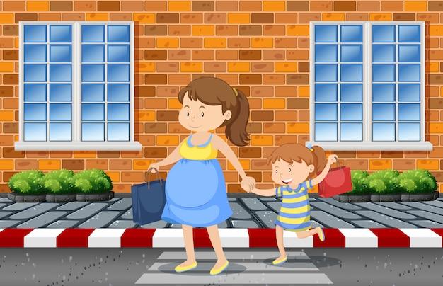 Mutter und tochter beim überqueren der straße