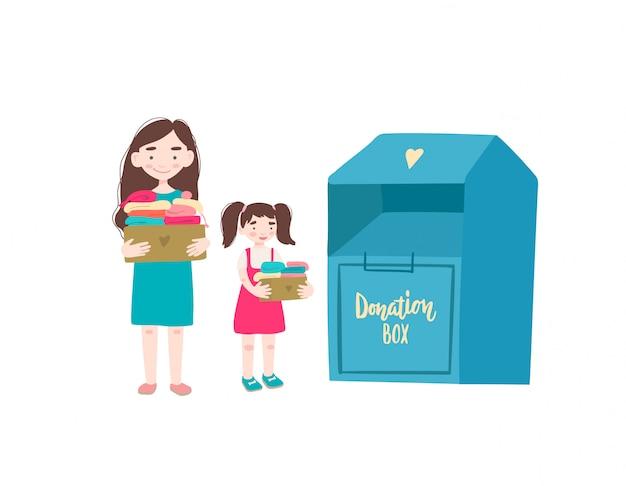 Mutter und tochter halten pappkartons mit kleidung zum spenden oder recycling und kleidungsbehälter.