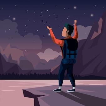 Nachtlandschaft des bergsteigermannes, der an der spitze des berges feiert