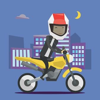 Nachts motorradfahren des jungen mannes.
