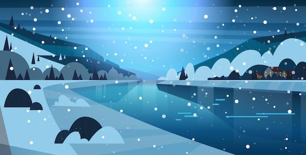 Nachtwinter-natur-landschaftshäuser auf gefrorenen fluss-hügeln und fallendem schnee