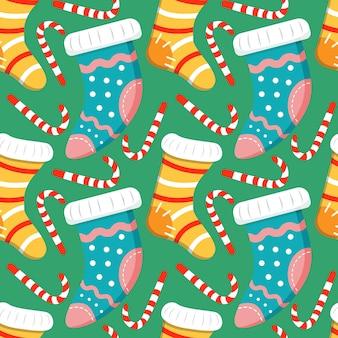 Nahtloser weihnachtshintergrund mit weihnachtlichen stricksocken mit mustern und zuckerstange gestreift