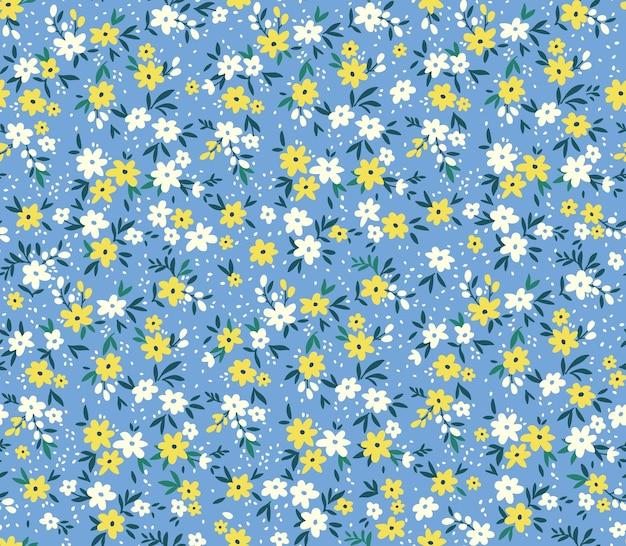 Nahtloses blumenmuster für design kleine gelbe und weiße blumen blauer hintergrund
