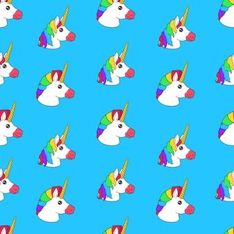 Nahtloses muster mit lustigem einhorn der karikatur mit regenbogenhaarschnitt auf blauem hintergrund