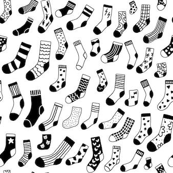 Nahtloses muster mit schwarzen und weißen doodle-socken mit unterschiedlicher textur. monochrome winterkleidungsstücke im skandinavischen stil.