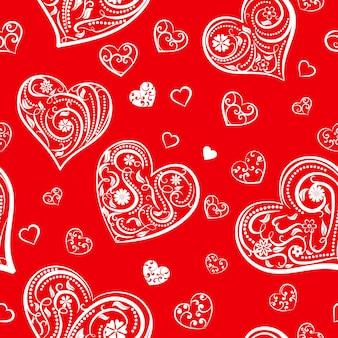 Nahtloses muster von großen und kleinen herzen mit ornament aus locken, blumen und blättern, weiß auf rot