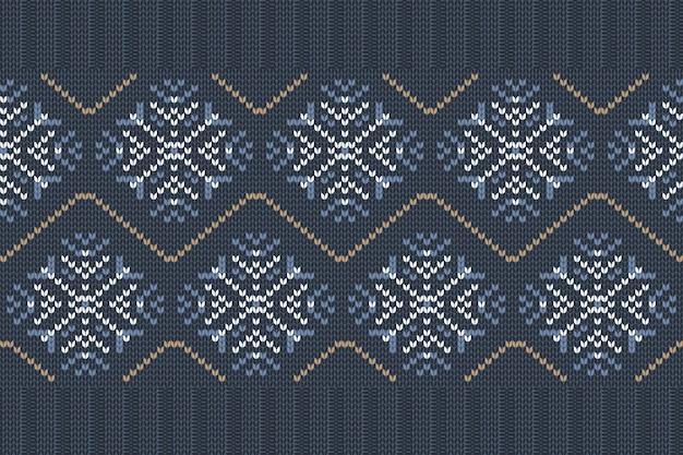 Nahtloses nordisches strickmuster in blauen, weißen farben mit schneeflocken.