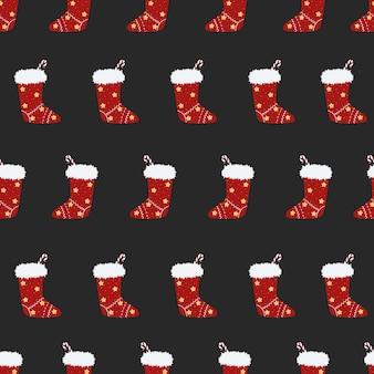 Nahtloses weihnachtsmuster mit geschenksocken auf blauem hintergrund rote neq-jahressocke mit süßigkeiten