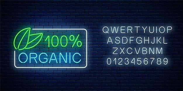 Neon 100 prozent bio-produktionsschild mit alphabet auf dunklem backsteinmauerhintergrund. naturkosmetik leuchtendes werbesymbol. vektor-illustration.