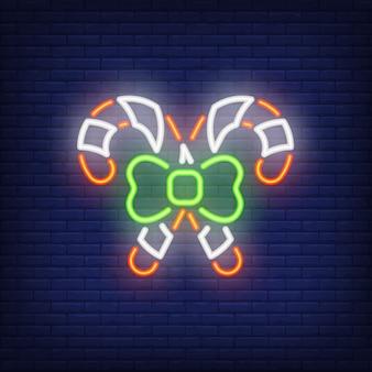 Neon kreuzte zuckerstangen mit bogen. festliches element. nacht helle werbung.