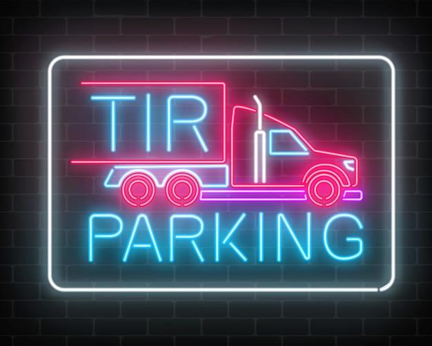 Neon leuchtendes tir-parkschild auf einer dunklen backsteinmauer glühendes schild eines langen fahrzeuglastwagens und von lastwagenfahrern.