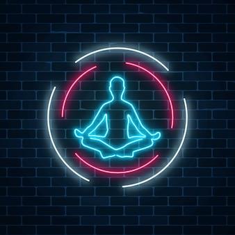Neon leuchtendes zeichen des yogaübungsclubs mit lotuspose in kreisrahmen auf dunklem backsteinmauerhintergrund.