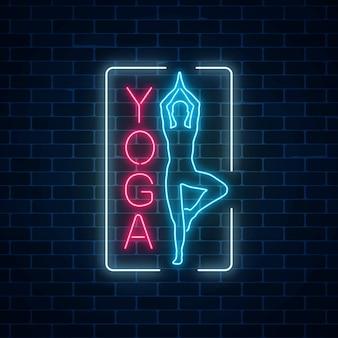 Neon leuchtendes zeichen von yogaübungen im rechteckrahmen auf dunklem backsteinmauerhintergrund.