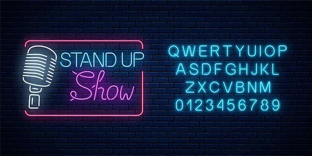 Neon-stand-up-show-zeichen mit retro-mikrofon auf einem backsteinmauerhintergrund. leuchtendes schild der comedy-schlacht mit alphabet.