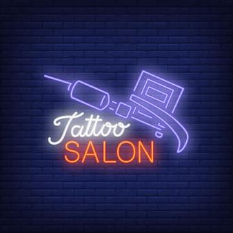 Neon-Text des Tätowierungssalons mit Tätowierungsmaschine. Leuchtreklame, Nacht helle Werbung