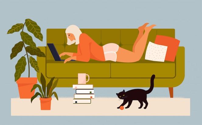 Nette junge frau, die am sofa mit laptop mit ihrer katze liegt