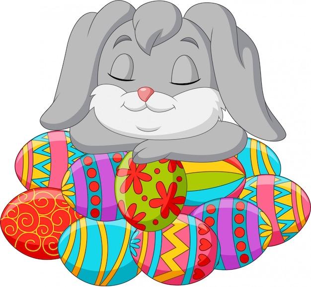 Nette kaninchenkarikatur, die auf ostereiern schläft
