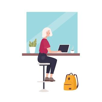 Nette lächelnde frau, die am café sitzt und am laptop arbeitet.