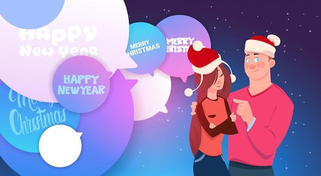 Nette paare in santa hats, die über chatblasen mit frohen weihnachten und guten rutsch ins neue jahr umfassen