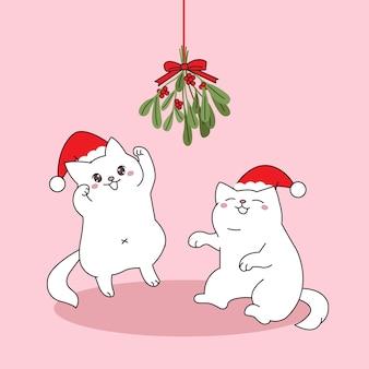 Nette paarkatze, die weihnachtsmannmütze trägt, die mit hängendem mistelzweig spielt.