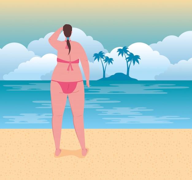Nette pralle frau im badeanzug rosa farbe am strand, sommerferienzeit