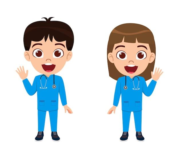 Nette schöne kinderjungen- und -mädchenschwester, die steht und winkt und mit krankenschwesterausstattungen zeigt, die mit stethoskop isoliert werden