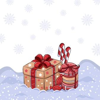 Nette winterbonbons und geschenkbox auf schnee