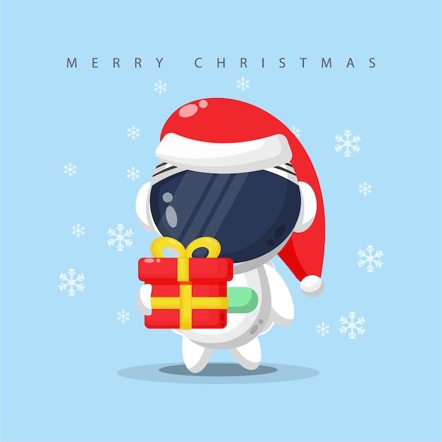 Netter astronaut, der eine geschenkbox am weihnachtstag trägt