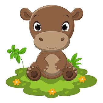 Netter baby-flusspferd-cartoon, der im gras sitzt