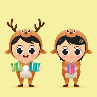 Netter charakterjunge und -mädchen der frohen weihnachten tragen rotwildkostüm