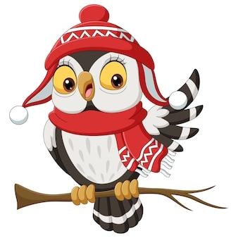 Netter eulenkarikatur, der einen schal und weihnachtsmütze auf ästen trägt